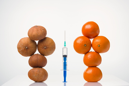 Wrinkled dried, smooth elastic tangerines in a female form and the syringe