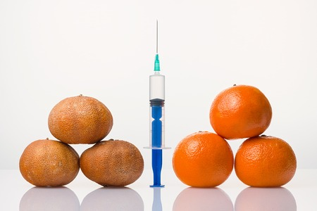 Wrinkled dried and smooth elastic tangerines the syringe Stock Photo