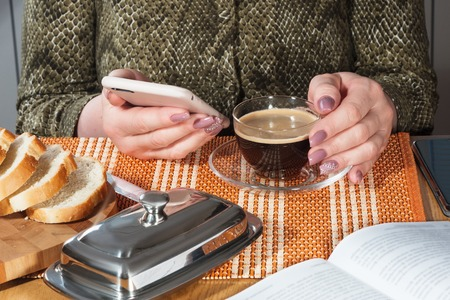 Glass cup with black coffee and phone in female hands with manicure Фото со стока
