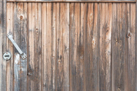 Background in style a rustic from old vertical wooden unpainted boards with the handle Фото со стока
