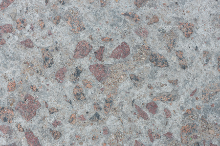 Background from concrete with large impregnations of red granite with an uneven surface Standard-Bild
