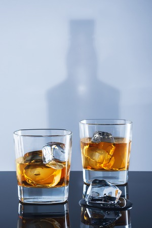 Two glasses of whisky and ice on a light background with a shadow from a bottle