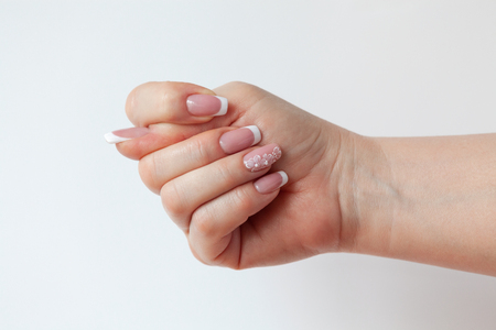 The beautiful female hand with graceful French manicure shows the sign of a fig