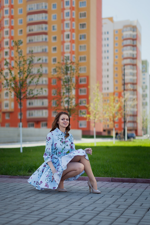 The beautiful girl sits in the blue short dress lifted by wind against the background of high houses