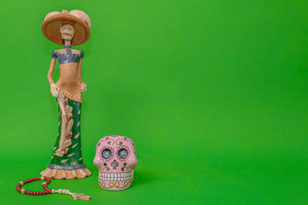 Calavera de la Catrina statuette, Mexican symbol of Day of the Dead, next to a wooden rosary and a pink skull, on a uniform green studio background Reklamní fotografie - 135498529