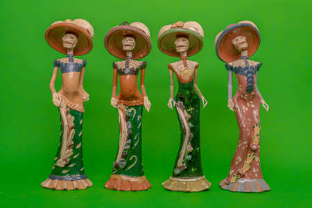 Four statuettes of Calaveras de la Catrina laughing at death, Mexican symbol of the Day of the Dead, on a uniform green studio background