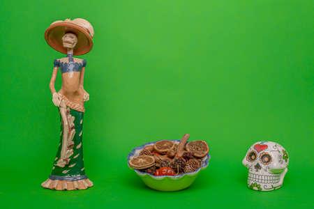 Calavera de la Catrina statuette, white skull and a bowl with three fruits, on a uniform green studio background Reklamní fotografie - 135498538