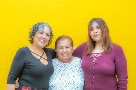 Daughter, grandmother and granddaughter hugging looking at the camera, three generations of Mexican women smiling in casual clothes on a yellow background