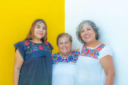 Großmutter zwischen Tochter und Enkelin sehr fröhlich, drei Generationen mexikanischer Frauen, die mit floral bedruckten Blusen auf weißem und gelbem Hintergrund lächeln