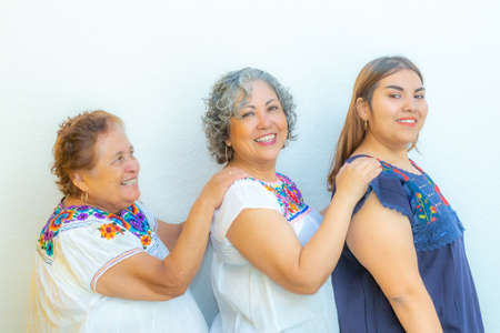 Three generations of smiling Mexican women with blouses with floral patterns in a row holding their shoulders against a white background Archivio Fotografico