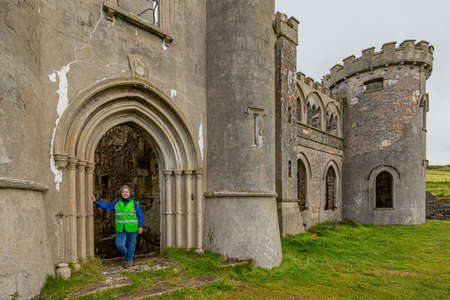 Female tourist at the arched gate of the ruined Clifden Castle with its gray walls, tower and windows, sunny spring day in County Galway, Ireland