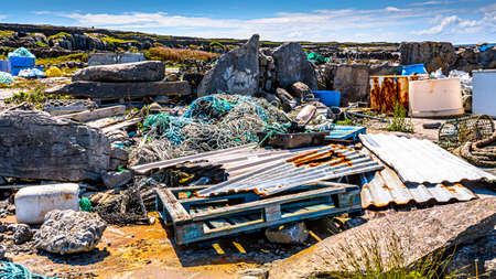 Accumulation of garbage such as wooden pallet, rusty metal sheets, fishing ropes, rusty fridges and a lot of garbage polluting the beautiful rocky coastal beach of the island of Inis Oirr, Ireland