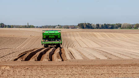 Rear view of a green tractor working on planting potatoes in an agricultural field, farmland with deep linear furrows in the ground, sunny day in Oensel, South Limburg, the Netherlands Holland Banco de Imagens
