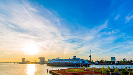 Cruise ship sailing on the new Maas river in a beautiful sunset. Harbor, streets, buildings and the Euromast tower with the sun covered by clouds on the horizon. Rotterdam, South Holland, Netherlands