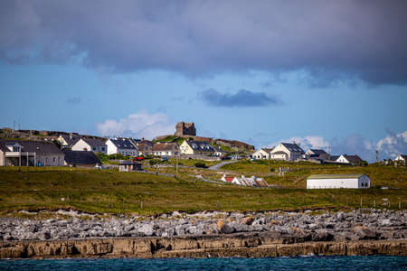Beautiful view of the Inis Oirr island with its houses and the ruined 15th-century castle tower in a prehistoric stone fort in the background, wonderful sunny day in Aran Islands, Ireland