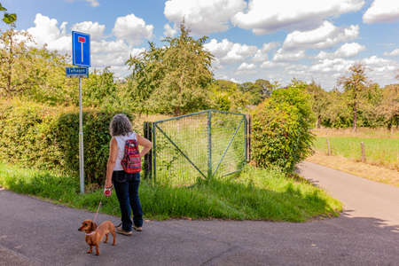 Mature woman with a backpack with her dog standing on a rural street looking at a sign indicating: this road is a dead end, abundant vegetation and trees on a sunny day in South Limburg, Netherlands