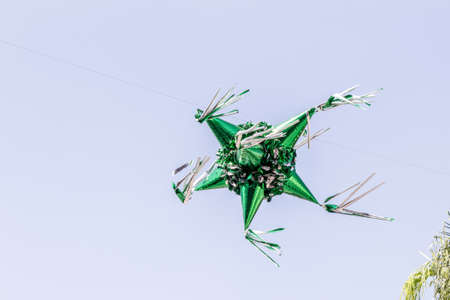 Metallic green paper piñata suspended in the air with a blue sky background, wonderful mexican tradition Stock Photo