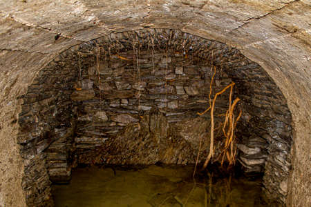 Underground stone canal with tree roots running through the walls with clear water in the Clervaux forest, Luxembourg