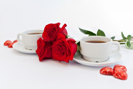 Red roses next to cups of tea photo