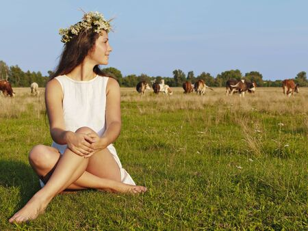 Girl sitting on the grass meadows  Evening light  In the background cows graze photo