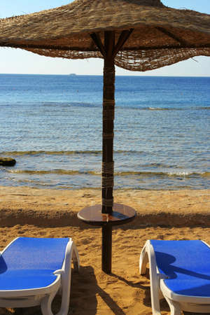 singleness: Two chairs and umbrella on the beach Stock Photo