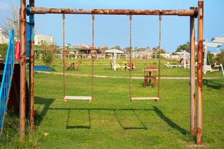 Old swing on the playground Фото со стока