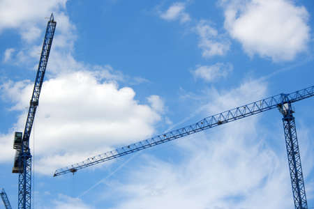 Two cranes on sky background photo