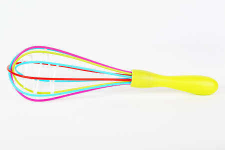 single whip: Colorful kitchen whisk on gray background