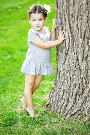 face in tree bark: Beautiful baby girl in the park