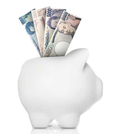 A white piggy bank filled with multiple bank notes. Stock Photo