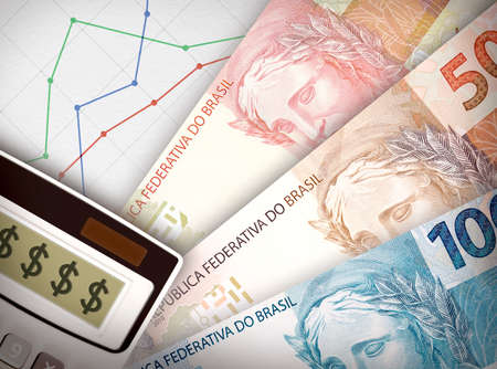 Three money bills in front of sheet of paper with a graph on it symbolizing economic relationships.