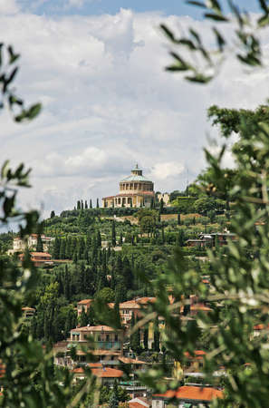 View of Tuscany with a domed building on top of a hill in a residential area full of cypresses and olive trees