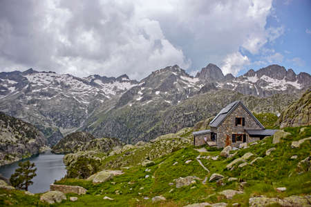 High mountain landscape with very high peaks and a lake on a stormy day and with a mountain hut in the foreground