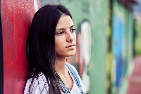 Young brunette Latina leaning against a wall of colored graffiti and looking forward in a denim sweater and a white blouse