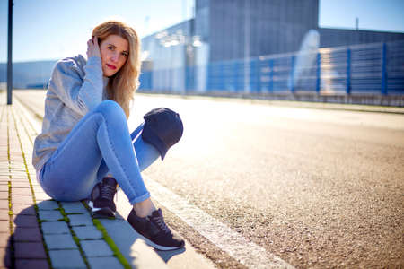 Girl with cap and long blonde hair, wearing jeans, sneakers and a sweatshirt, sitting on the sidewalk in an empty urban area on a very sunny day