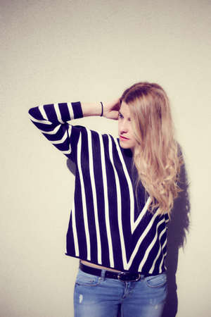 Long hair blonde model girl next to a wall posing with a striped sweater and jeans on a very sunny day