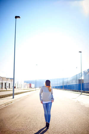 Girl with cap and long blonde hair, wearing jeans, sneakers and sweatshirt, walking down the street in an empty urban area on a very sunny day Stock Photo