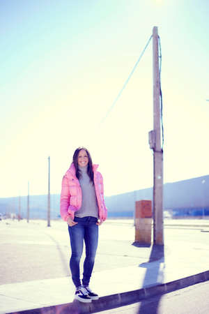 Young girl with long hair in a pink jacket, jeans and sneakers, in an urban area with a very sunny day and waiting on the sidewalk Archivio Fotografico