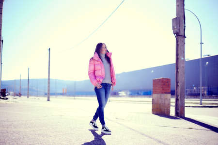 Young girl with long hair in a pink jacket, jeans and sneakers, in an urban area with a very sunny day and walking on the sidewalk