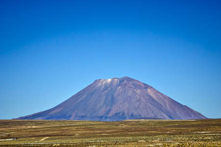 Arid landscape with a purple-toned volcano seen from the front with a blue sky without any clouds
