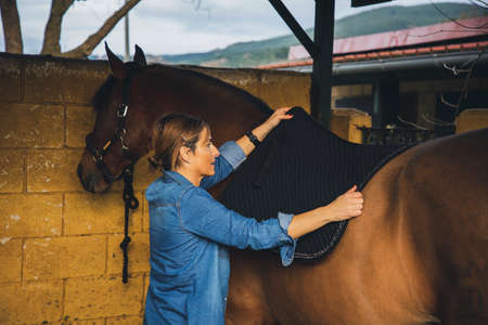 Woman dressed in denim and fringed boots saddling her horse and preparing it for a ride