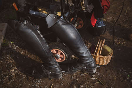 Black riding boots with other riding equipment