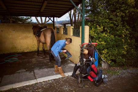 Riding woman dressed in cowboy clothes cleaning her riding boots with her horse tied to the bottom of the stable prepared with the saddle
