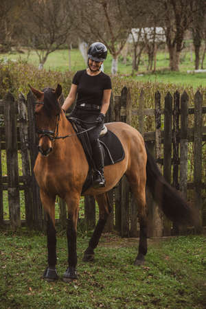 Woman rider on her brown horse dressed in black with a black hoof smiling in front of a rustic wooden fence at the country ranch