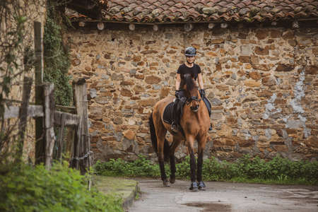 Female rider dressed in black with her brown horse riding through a village with stone walls