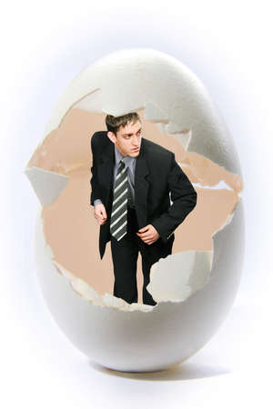 Businessman standing in a big egg shell Stock Photo