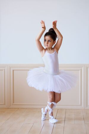 Little girl ballerina in a white tutu is on the floor in ballet class. 写真素材