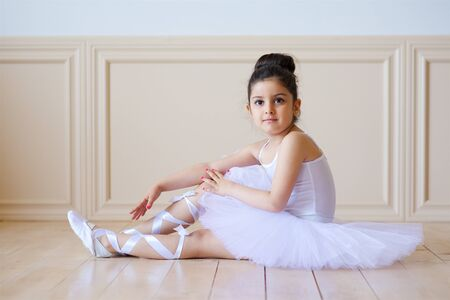 Little girl ballerina in white tutu sitting on floor in ballet class. Standard-Bild