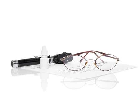 examen de la vista: Gafas, oftalmoscopio y una botella de gotas para los ojos son en un examen de la vista Foto de archivo