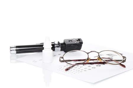 prueba de vision: Gafas, oftalmoscopio y una botella de gotas para los ojos son en un examen de la vista Foto de archivo